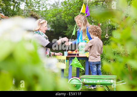 Grandmother buying lemonade from grandchildren's stand - Stock Photo