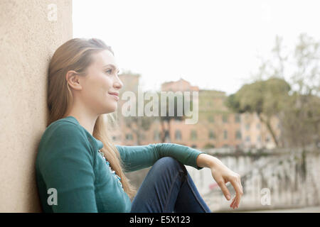 Young woman leaning against wall, Isola Tiberina, Rome, Italy - Stock Photo