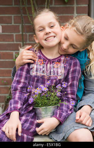 Two sisters with flower pot plant in garden - Stock Photo