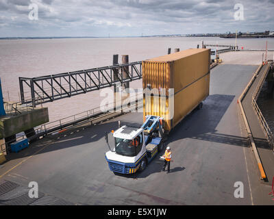 Elevated view of truck and shipping container on ramp to ship - Stock Photo