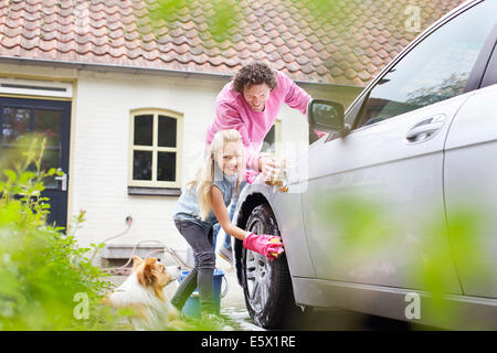Girl helping father wash his car - Stock Photo