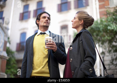 Businessman and woman chatting on street - Stock Photo
