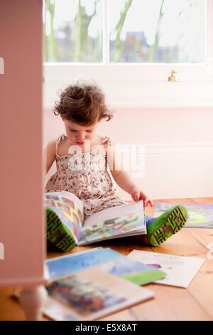 Female toddler reading storybooks in bedroom - Stock Photo