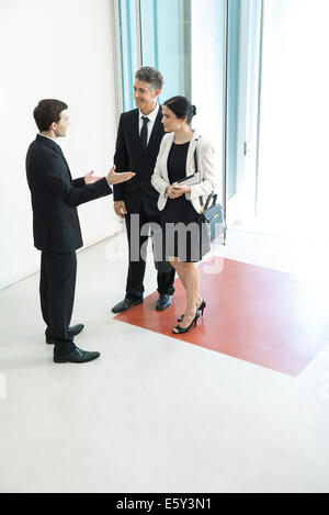 Greeter directing attendees as they arrive for conference - Stock Photo