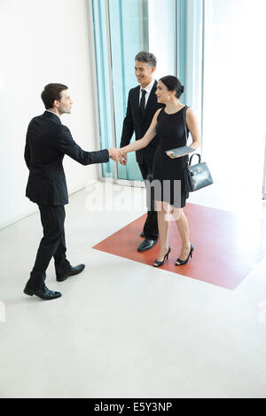 Greeter meeting attendees as they arrive for conference - Stock Photo