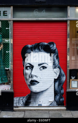 Retro style graffiti on the shutters of a branch of Armstrongs Vintage clothing store in Edinburgh. - Stock Photo