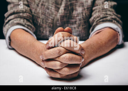 Studio photography of praying hands of a senior woman on table. Old hands clasped on a table. - Stock Photo