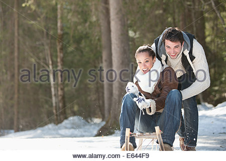 Smiling couple sledding in snowy field - Stock Photo