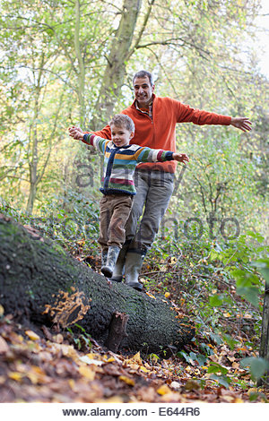 Father helping son cross log outdoors - Stock Photo
