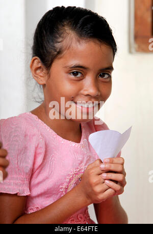 Young girl holds a heart of paper. Dili, East Timor, Timor Leste - Stock Photo