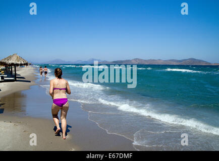 People running along Tingaki Beach, Tingaki, Kos Island, Greece. - Stock Photo