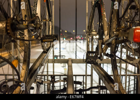 Detail of the pedals and chain of bikes parked over the train lines covered with snow in Aarhus, Denmark, Europe - Stock Photo