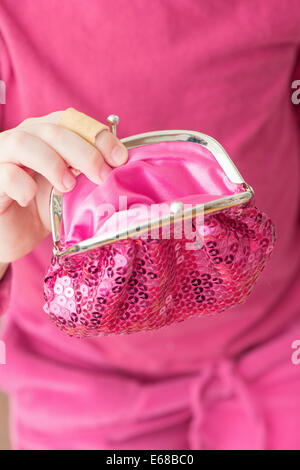 Hand of little girl holding pink change purse - Stock Photo