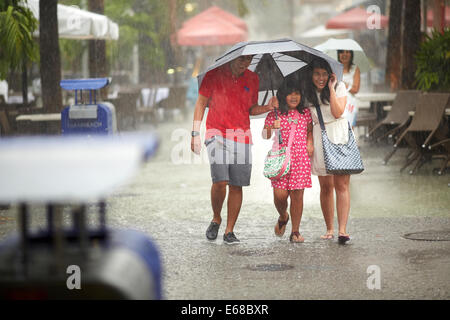 Family shelter from tropical rain storm under a umbrella on the streets of Miami, Florida - Stock Photo