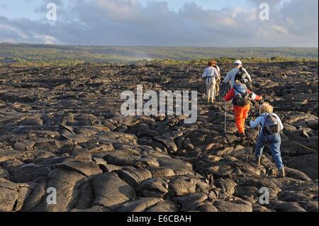 Group of hikers walking on cooled pahoehoe lava flow at sunrise, Kilauea Volcano, Big Island, Hawaii Volcanoes National - Stock Photo