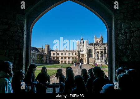 A crowd of tourists looking through a stone archway at Trinity College and the Grand Court, University of Cambridge, - Stock Photo