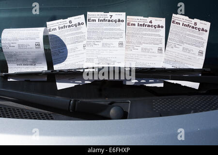 Multiple parking tickets under the windscreen wiper of a car parked in Calheta, Madeira. - Stock Photo