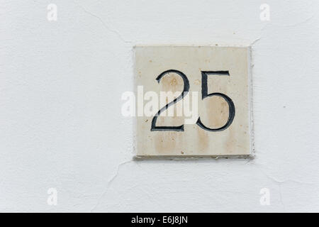 House number twenty five on a stone plaque with a green wall background - Stock Photo