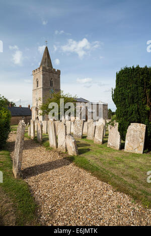 The village church of St Mary the Virgin on a summer evening with gravestones lining a gravel path, Morcott in Rutland, - Stock Photo