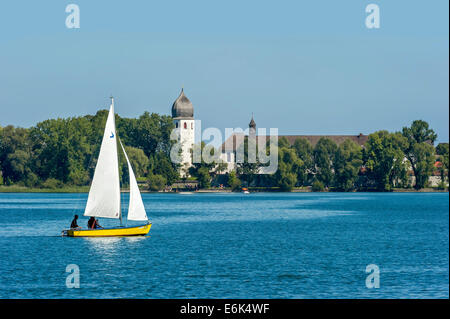 Sailboat in front of the bell tower of Frauenwörth Abbey, Frauenchiemsee Island, Lake Chiemsee, Chiemgau, Upper - Stock Photo