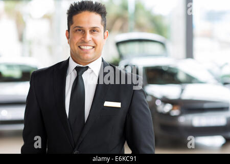 happy young Indian car salesman in showroom - Stock Photo