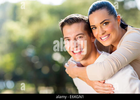 happy woman enjoying piggyback ride on boyfriends back outdoors - Stock Photo