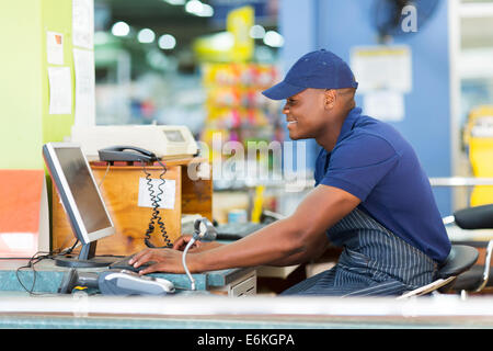 happy African male cashier working at till point in supermarket - Stock Photo