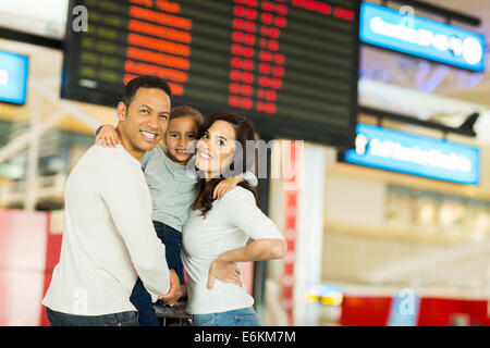 portrait of young family in front of flight information board at airport - Stock Photo