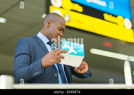 professional African American business traveller checking time at airport - Stock Photo
