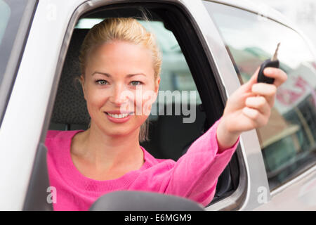 Caucasian lady showing a car key. - Stock Photo