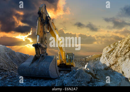 Image of a tracked excavator in a quarry with a setting sun and light rays - Stock Photo