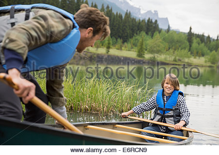 Father helping son out of canoe - Stock Photo
