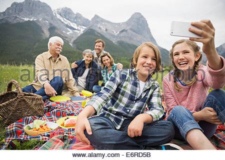 Family having picnic in rural field - Stock Photo