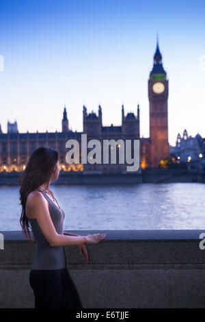 A young woman standing in front of the Houses of Parliament in London at dusk - Stock Photo
