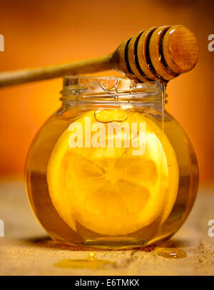 Glass jar of honey with wooden drizzler and slice of lemon on old wooden background. - Stock Photo
