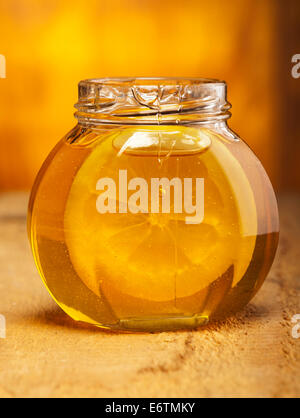 Glass jar of honey with slice of lemon on old wooden background. - Stock Photo