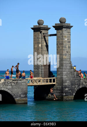 Local children and young people bathing at the Puente de las Bolas, stone gate outside the fort Castillo de San - Stock Photo