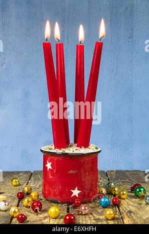 Four red christmas candles on a wooden blue background with old christmas balls for decoration - Stock Photo