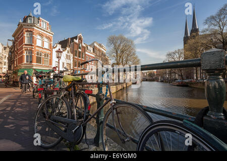 AMSTERDAM, NETHERLANDS - MARCH 19, 2014: Colorful houses on the canal in spring sunny day. Bicycles stand parked - Stock Photo