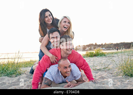 Group of friends making human pile on beach - Stock Photo