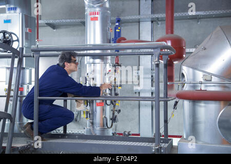 Engineer inspecting equipment from access platform in power station - Stock Photo