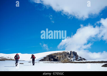 Two men hiking in snow, Bucegi Mountains, Transylvania, Romania - Stock Photo