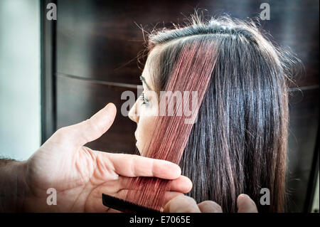 Male hairdresser combing young woman's hair in hair salon - Stock Photo