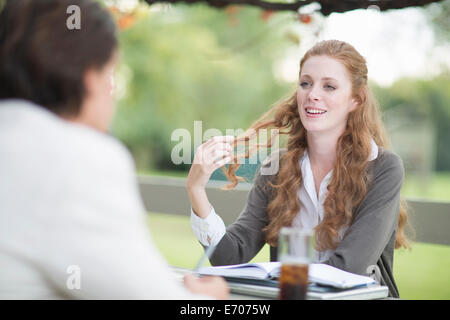 Over the shoulder view of businessman and female colleague having informal meeting in garden - Stock Photo