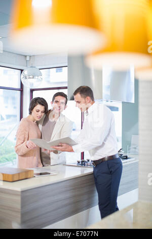 Mid adult couple and salesman looking at brochure in kitchen showroom - Stock Photo