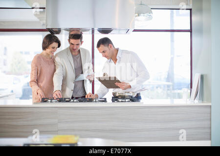 Mid adult couple and salesman looking at hob in kitchen showroom - Stock Photo