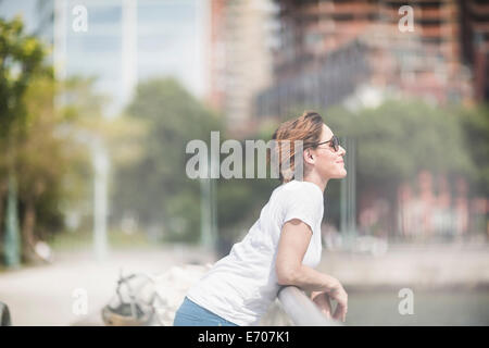 Smiling mid adult woman leaning on city railings - Stock Photo