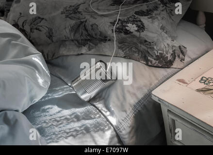 tin can telephone on bed - Stock Photo