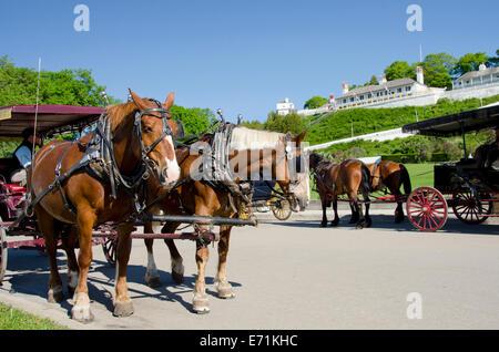 USA, Michigan, Mackinac Island. Traditional horse carriages on Main Street (aka Huron) with historic Fort Mackinac. - Stock Photo