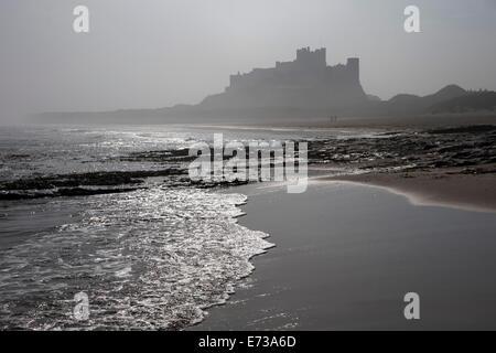 Waves breaking at Bamburgh Beach looking towards Bamburgh Castle on a misty morning, Northumberland, England, United - Stock Photo